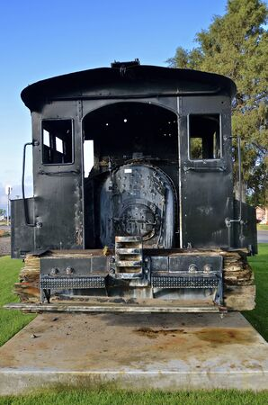 A very old black coal and steam powered locomotive rests on a concrete pad,