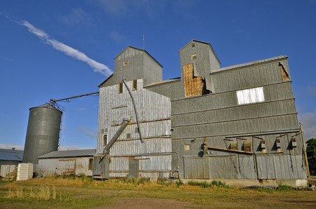 An antiquated elevator system consists of various grain bins, tanks, and augers.