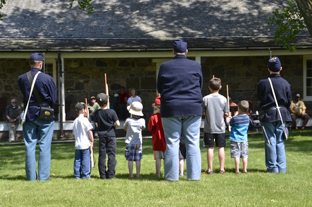 reenact: FORT SISSETON, SOUTH DAKOTA - June 6, 2015:  7th Cavalry offiecers reenact the process of of military training to volunteer youngsters at the annual Fort Sisseton Historical Rendezvous held annually the first full weekend of June.