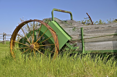 spoked: An old wooden manure spreader with steel spoked wheels  is left parked in the long grass