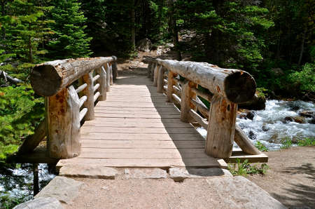 Wooden log bridge spans a mountain stream and leads to a hiking path.
