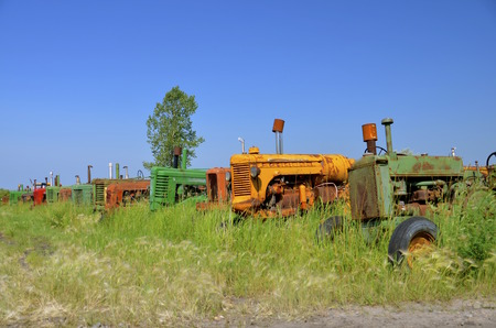 junked: Old junked tractors in various colors are parked in a row at a salvage  yard. Stock Photo