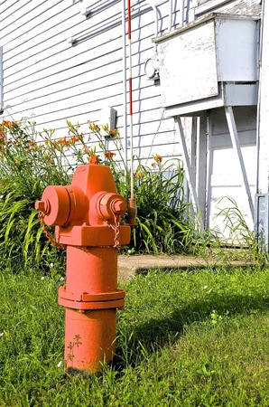 old fire hydrant: An orange  fire hydrant is in front of an old painted white house with an air conditioner box and orange tiger lilies Stock Photo