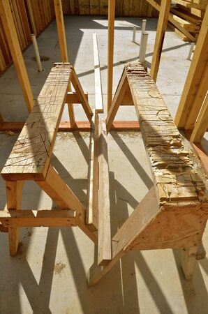 sawhorse: Deep cuts into wooden sawhorse which are being used to frame an apartment complex