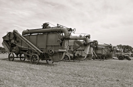 machines: Threshing machines lined up in a field of wheat stubble