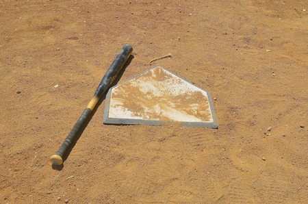 A wooden baseball bat is left lying on a sand covered home plate.