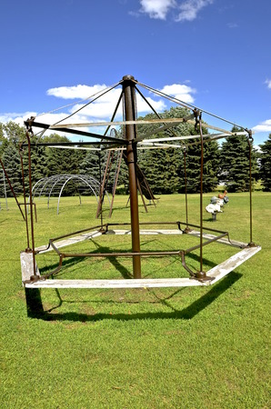 jungle gyms: An old hexagonal merry-go-round in a park is in functional working condition.