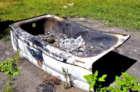 An old white bath tub full of soot and ashes is being used as a burn barrel of trash, garbage, and  rubbish on a farm.