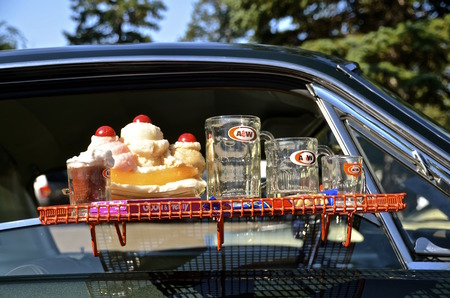 root beer: BISMARCK, NORTH DAKOTA, August 1, 2015:  The Mustang and Ford car show takes place yearly on the capital grounds during the Capital AFair and finds a Ford car with a A  W Root Beer platter attached to a window.