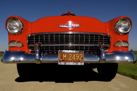 A red 1955 classic Chevrolet auto exposes the front , grill and number Stock Photo