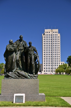 pioneers: Bismarck, North Dakota capital building and ground with a statue honoring the early pioneers.