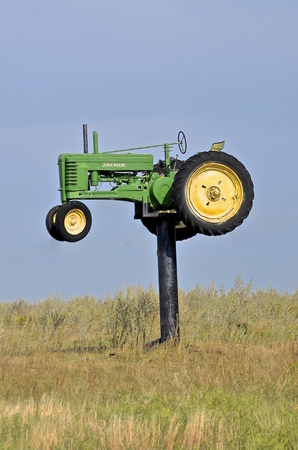 EDGELY, NORTH DAKOTA,  Aug 30, 2015: . An old John Deere tractor rises high into the sky as it rests on a steel beam and supported platform where it draws attention to the arrival into the agricultural rural town of Edgely. Editorial