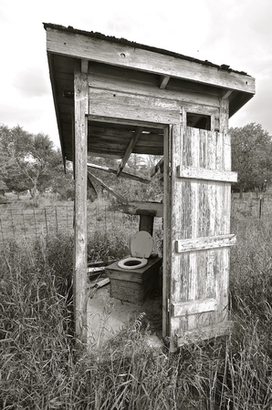 Black and White A falling apart outhouse with a missing wall used a toiled seat cover on the bench