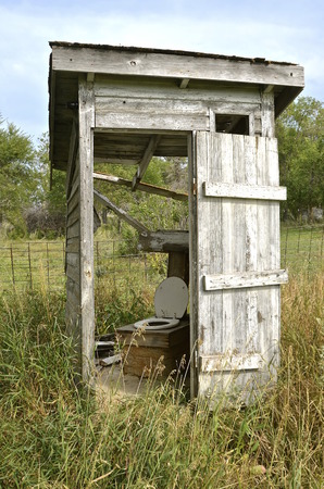 latrine: A falling apart outhouse with a missing wall used a toiled seat cover on the bench Stock Photo