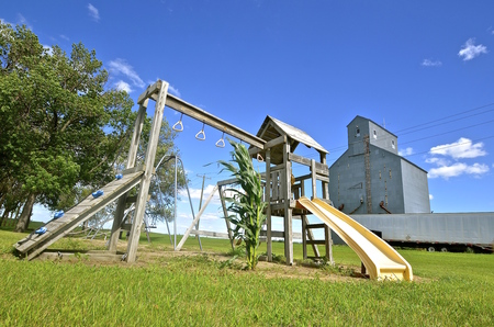 rural town: A lone stalk of corn grows under monkey bars and an old abandoned grain elevator in the background are found in a small rural town park playground. Stock Photo