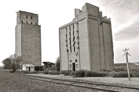 elevators: Two old poured concrete elevators stand deserted and empty along a railroad track.   black and white