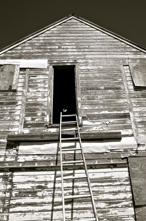 rungs: A crooked aluminum ladder reaches to an upper level old granary door
