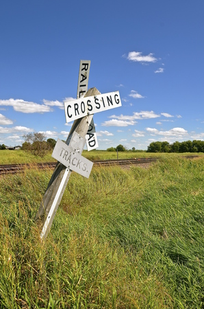 dangerously: A railroad crossing sign is leaning dangerously close to toppling over in front of a railroad track.