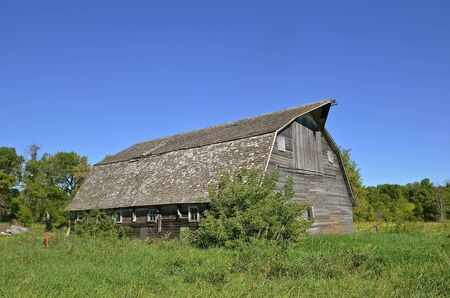 disrepair: A very old weathered  barn in a state of disrepair need shingles for survival.