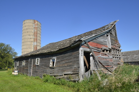 disrepair: A very old weathered  barn  in a state of disrepair is ready for demolition.