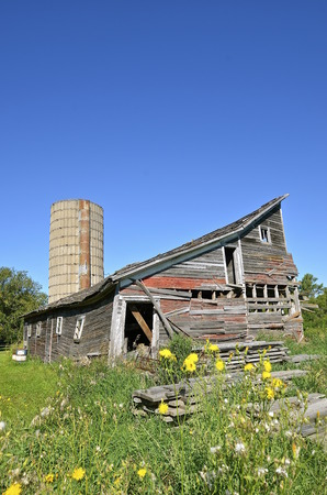 rickety: A rickety old barn and silo is in need of disrepair and ready for demolition. Stock Photo