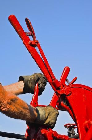 증기 탈수기의 동창회에서 빨간색 타작 기계의 기어를 작동하는 남자의 낀된 손 스톡 콘텐츠