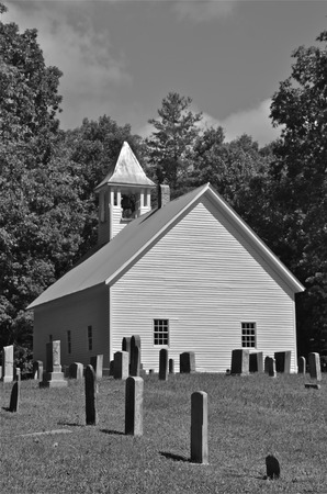head stones: black and white A graveyard with old head stones is located behind a white church building.