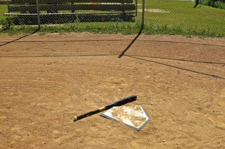 backstop: Bat and sand on home plate on a playground with a bleacher in the background