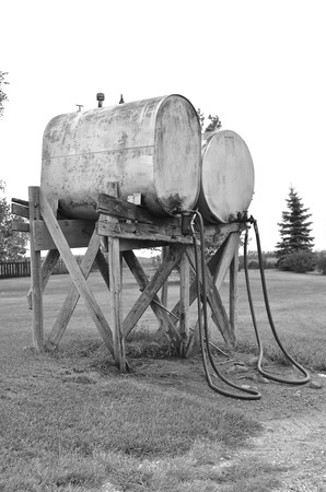Old fuel tanks on a farm with hoses which lay on the ground black and white
