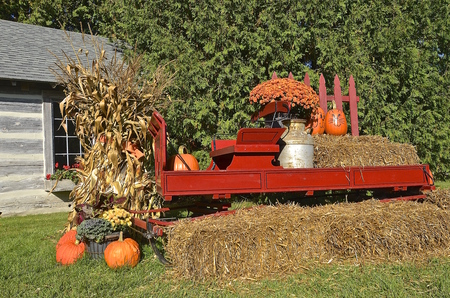 shocks: les of straw, gourds, a bright red wagon, and pumpkins  create a fall autumn scene.