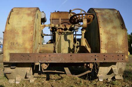 maldestro: Un vecchio trattore primitivo espone enormi parafanghi oltre ruote e alette in acciaio