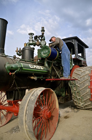 thresh: ROLLAG, MN, Sept 3, 2015: A steam engine is being serviced  at the West Central Steam Threshers ReunionWCSTR where 1000s attend each Labor Day weekend in Rollag, MN each year.