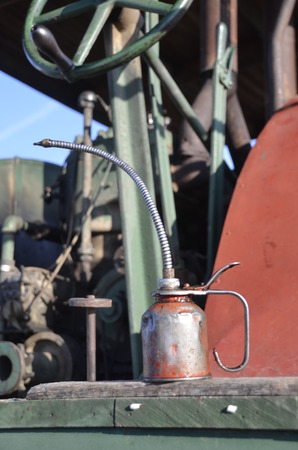 lubricate: A long stemmed oil can rests on the platform of an old steam engine Stock Photo
