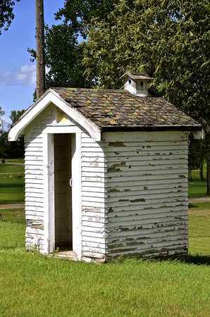 latrine: Old outdoor outhouse with chimney birdhouse