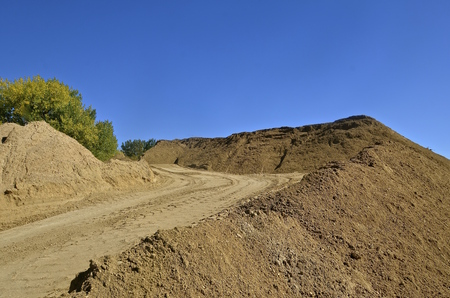 A graded road leads to the top of a temporary pile of sand which is to be used for road construction and salting.