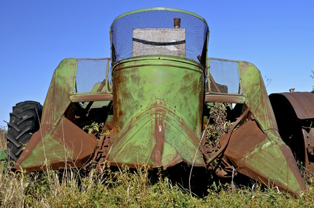 implementing: An old mounted green corn picker is mounted on the front end of a a tractor