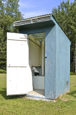 latrine: Functional painted old outhouse with bench and toilet tissue