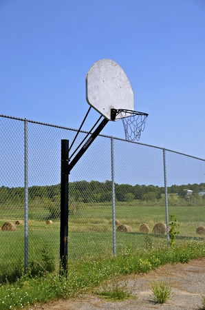 fenced in: Neglected rural basketball backboard on a fenced tennis court with a field of shocked grain in the background. Stock Photo