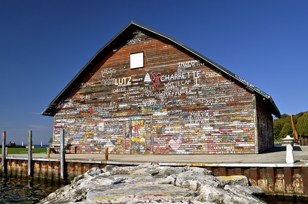 autograph: An old building on a pier is full of painted autographs and graffiti,