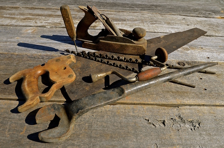 A collection of old hand woodworking tools such as a plane, saw, wrench,  brace and bits. 版權商用圖片