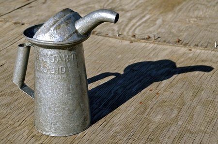 lubricate: An old galvanized metal quart oil can cast its shadow