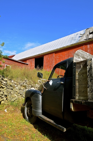 dairying: An old black truck is parked in front of a huge deteriorating red barn