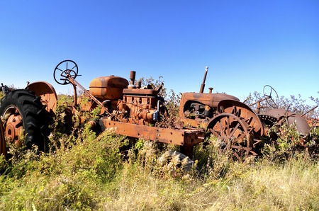 junkyard: Old orange tractors left in the junkyard for parts and salvage