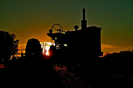 int: Old tractor silhouetted int he sunset