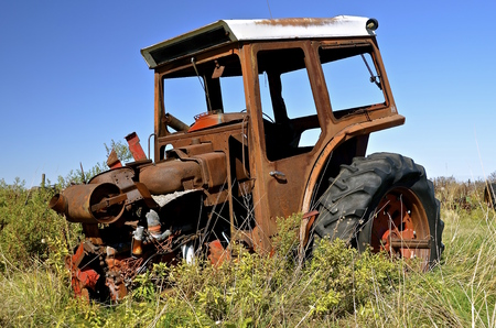 front end: An old tractor with a cab is missing the front end and wheels Stock Photo
