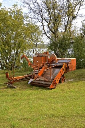 Old orange power take off threshing machine Banco de Imagens