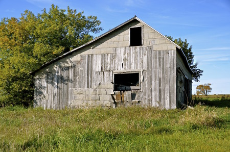 haymow: Old weathered abandoned  barn with open doors