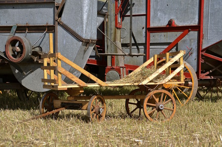 shocks: Mini straw rack parked alongside an old threshing machine.