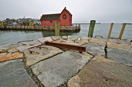 pilings: Anchor lies on the top of  rock seawall with Motif One of Rockport in the background. Stock Photo