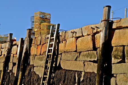 lobster pot: A ladder leans against a seawall exposing the players of patina on the rock with lobster traps resting on the ledge. Stock Photo